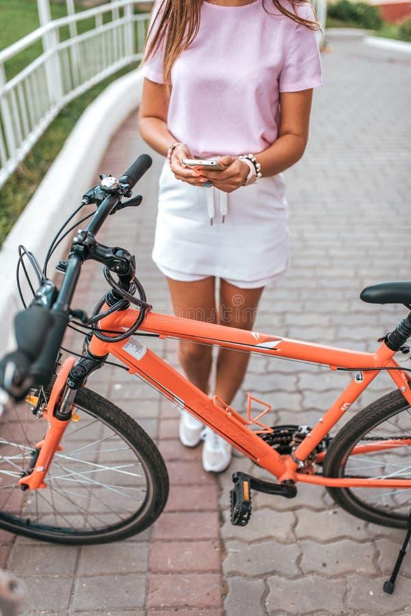 Una ragazza tiene un telefono in sue mani, prende le immagini di un parcheggio della bicicletta, un modulo di iscrizione online a fotografia stock libera da diritti