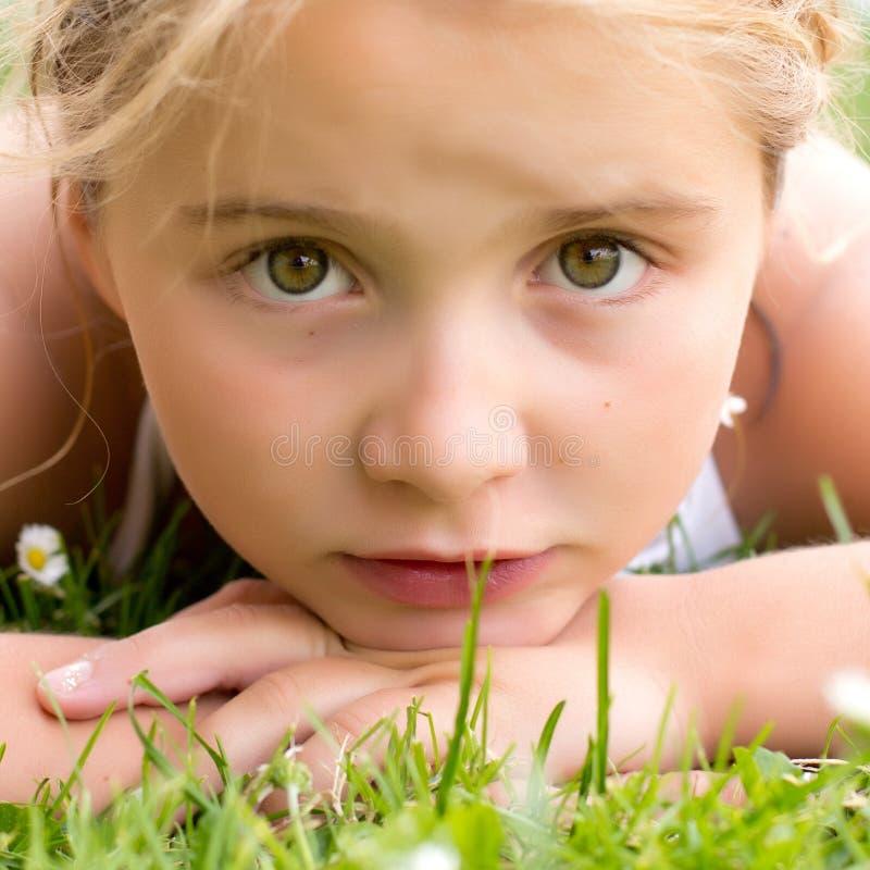 Una ragazza triste del bambino in erba fotografia stock libera da diritti