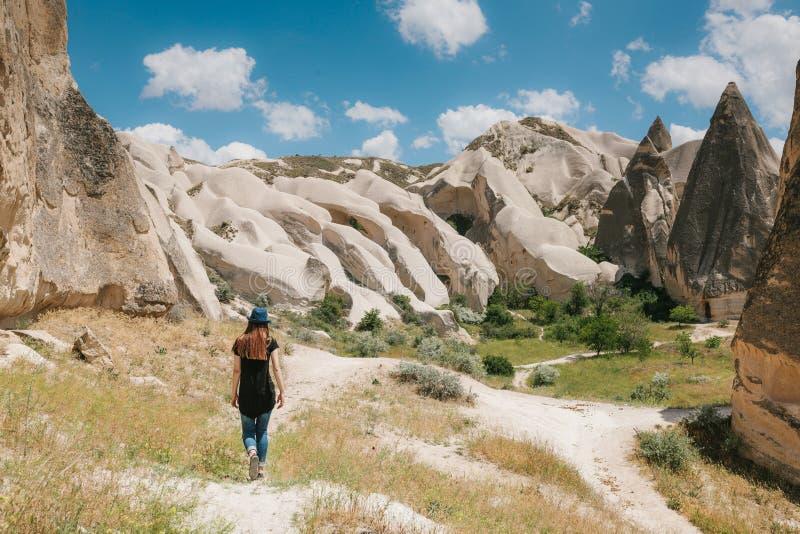 Una ragazza turistica cammina lungo la strada accanto alle colline meravigliose di Cappadocia in Turchia ed ammira la bellezza in fotografia stock