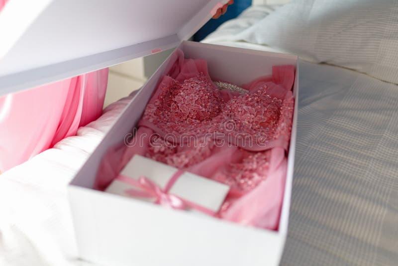 Una ragazza in un abito rosa apre una scatola bianca con un arco con un nuovo interno rosa del vestito, libera un arco sul conten fotografie stock libere da diritti