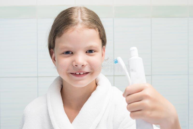 Una ragazza in un accappatoio bianco nel bagno tiene il dentifricio in pasta e una spazzola in sua mano fotografia stock libera da diritti