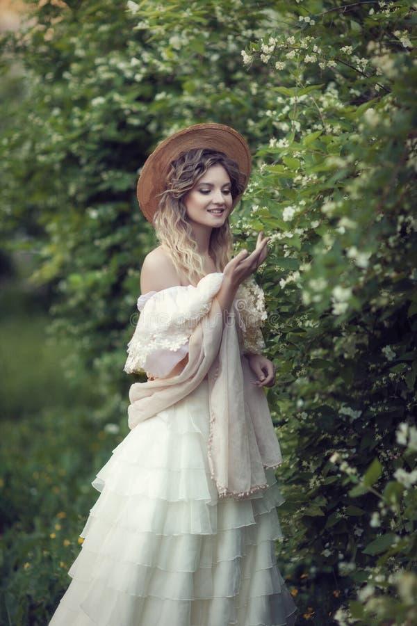 Una ragazza in un bello vestito d'annata con i fiori del gelsomino fotografie stock