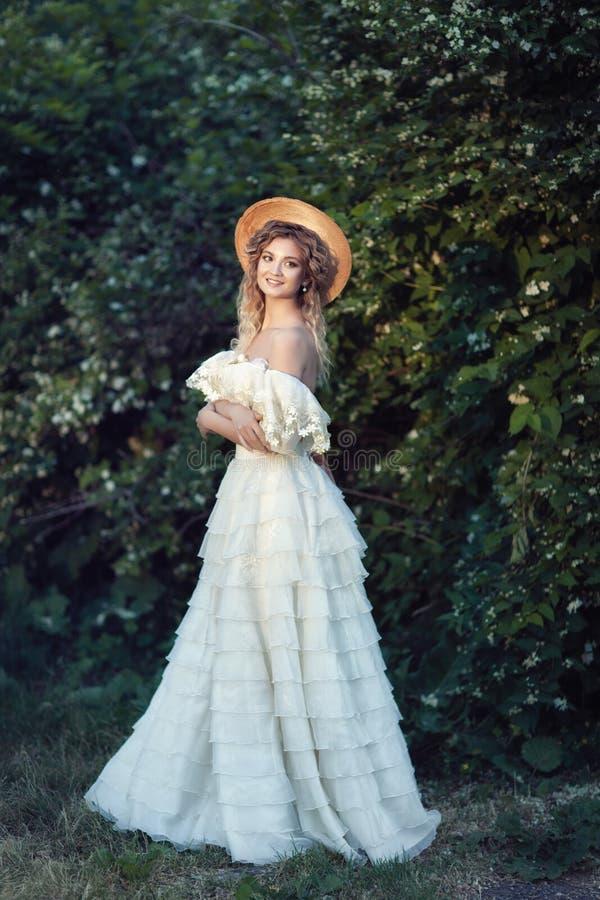 Una ragazza in un bello vestito d'annata con i fiori del gelsomino immagine stock