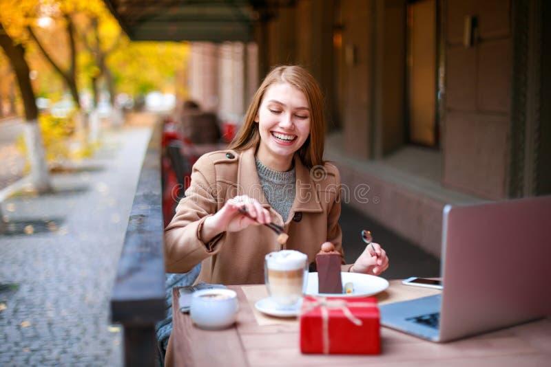 Una ragazza in un caffè all'aperto con un computer portatile che parla con qualcuno con una video chiamata, in lats che gettano z fotografia stock