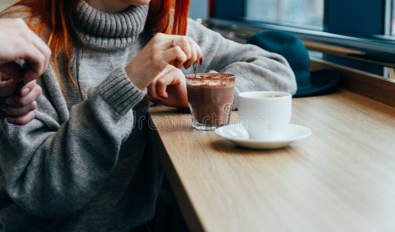 una ragazza in un caffè si mescola, mangiando un cucchiaio della cioccolata calda il tipo apre lo zucchero per caffè, tè in una t fotografie stock libere da diritti