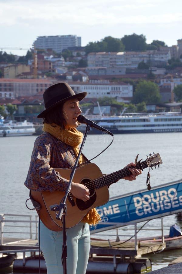 Una ragazza in un cappello con una chitarra canta le canzoni liriche sull'argine del fiume del Duero nella città di Oporto fotografia stock libera da diritti