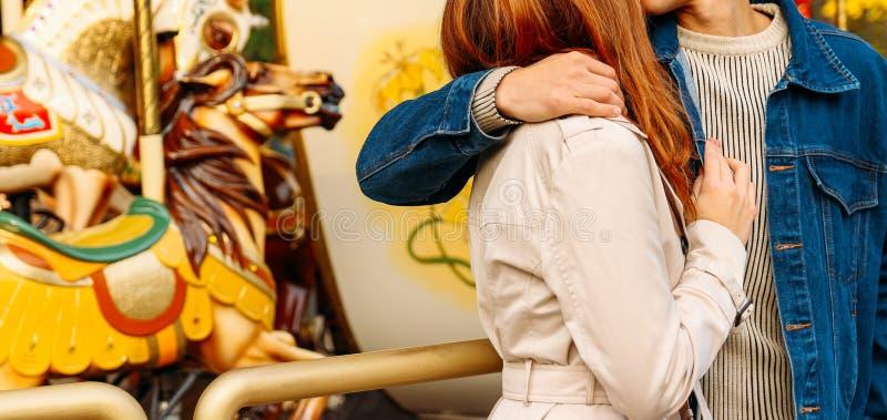Una ragazza in un cappotto beige e un tipo in un rivestimento del denim che abbraccia in mezzo di un parco di divertimenti, un gi immagini stock libere da diritti