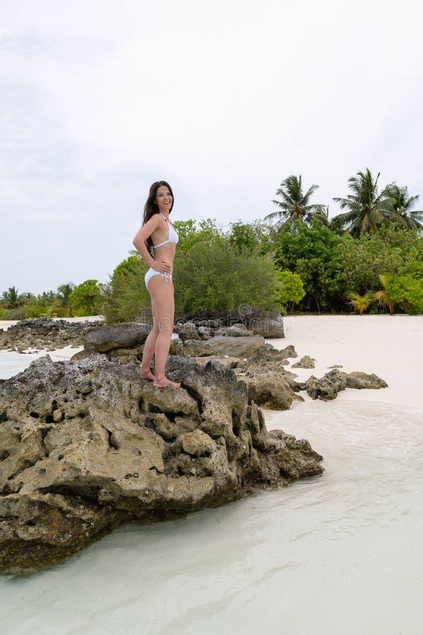 Una ragazza in un costume da bagno bianco che sta su una pietra sulla spiaggia e che sorride felicemente fotografie stock