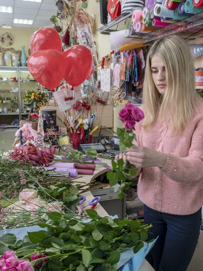 Una ragazza, un fiorista-progettista dà un bello, mazzo festivo dei fiori rossi e un cuore con l'amore dell'iscrizione, specialme fotografia stock