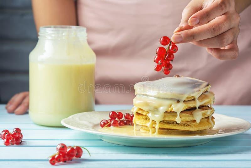 Una ragazza in un grembiule rosa decora i pancake con il ribes rosso Pancake saporiti della prima colazione sana con latte conden immagini stock