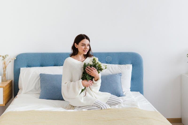 Una ragazza in un maglione bianco si siede su un letto che tiene un mazzo delle rose bianche in sua mano immagine stock libera da diritti