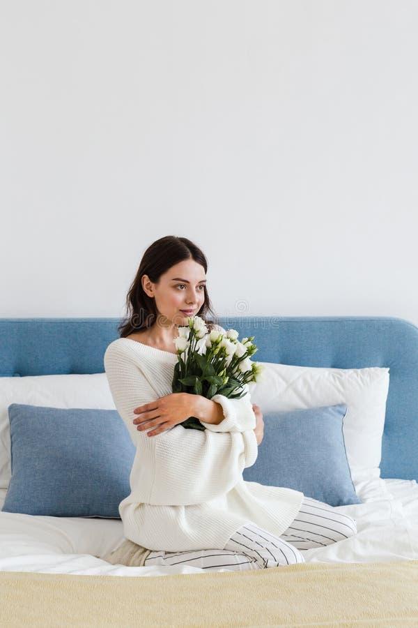 Una ragazza in un maglione bianco si siede su un letto che tiene un mazzo delle rose bianche in sua mano immagine stock