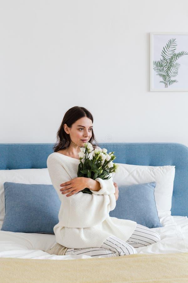 Una ragazza in un maglione bianco si siede su un letto che tiene un mazzo delle rose bianche in sua mano fotografie stock