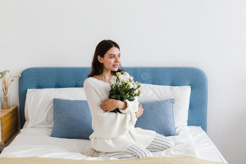 Una ragazza in un maglione bianco si siede su un letto che tiene un mazzo delle rose bianche in sua mano fotografia stock libera da diritti