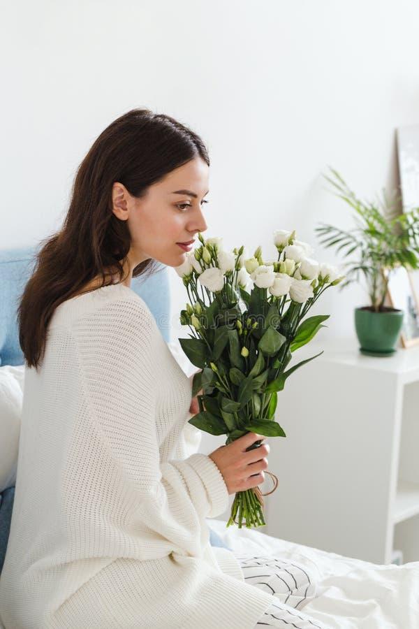 Una ragazza in un maglione bianco si siede su un letto che tiene un mazzo delle rose bianche in sua mano immagini stock libere da diritti
