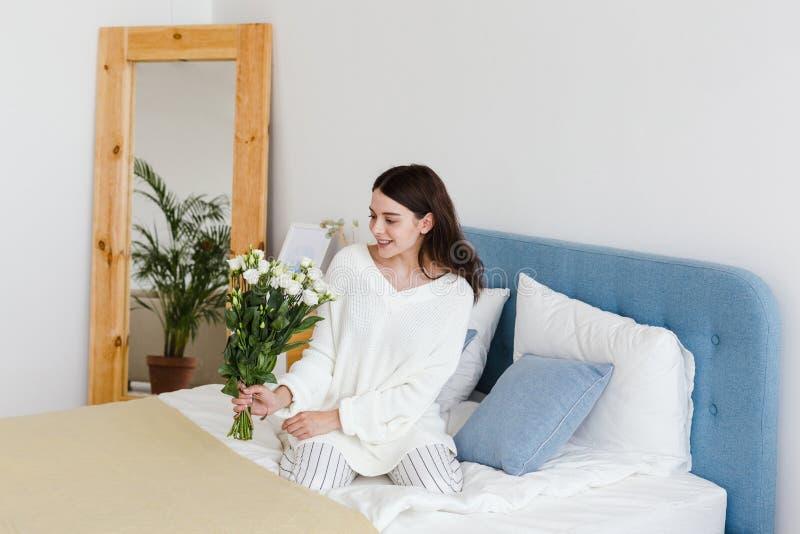 Una ragazza in un maglione bianco si siede su un letto che tiene un mazzo delle rose bianche in sua mano fotografia stock