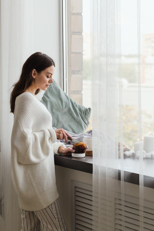 Una ragazza in un maglione bianco sta vicino alla finestra e taglia un bigné immagini stock