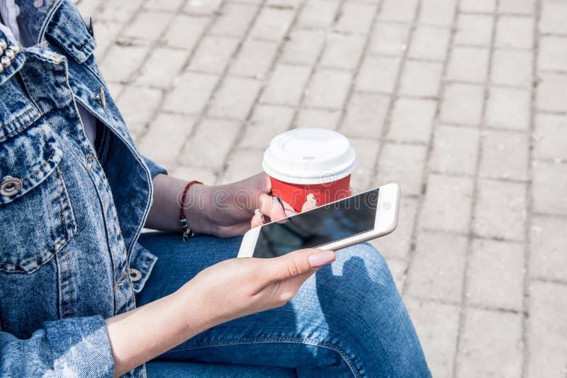 Una ragazza in un rivestimento del denim cammina giù la via con caffè e un telefono in sue mani Ragazza in vetri ed in un rivesti fotografia stock libera da diritti