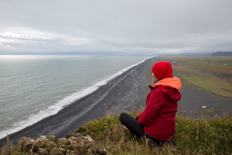 Una ragazza in un rivestimento rosso si siede su una scogliera sopra la riva di mare con la sabbia nera della lava che allunga al fotografie stock