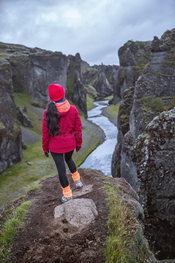 Una ragazza in un rivestimento rosso sta sull'orlo di una gola profonda L'Islanda contenuta immagine fotografia stock