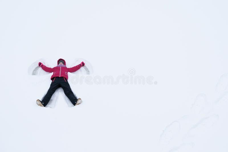 Una ragazza in un rivestimento rosso sta trovandosi nella neve che fa una figura di angelo con il suo corpo immagini stock