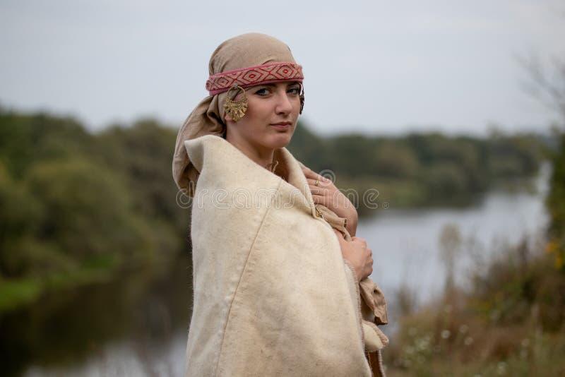 Una ragazza in un vecchio copricapo dello slavo e mantello dell'era di Viking sulla sponda del fiume fotografia stock