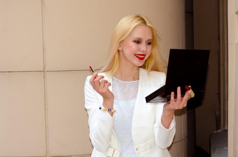 Una ragazza in un vestito bianco fa un trucco ed ammira l'esame sé nello specchio fotografia stock