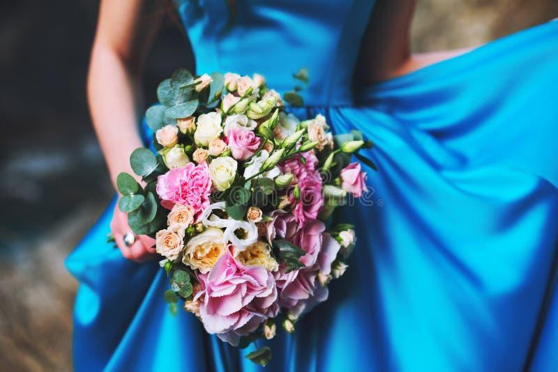 Una ragazza in un vestito blu sta tenendo un mazzo di nozze dei fiori dalle rose fotografia stock libera da diritti