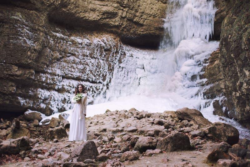 Una ragazza in un vestito da sposa con un mazzo dei fiori su un fondo di un ghiacciaio immagini stock libere da diritti
