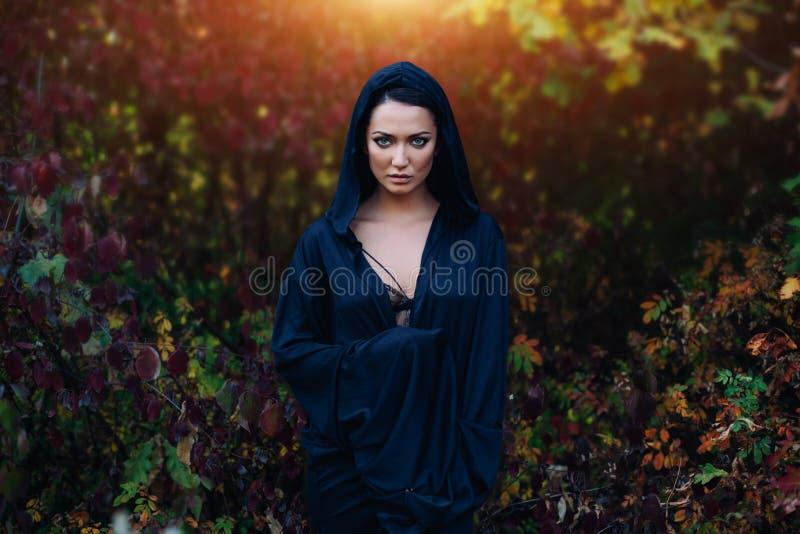 Una ragazza in un vestito nero, un mantello con un cappuccio Sta contro lo sfondo della foresta di autunno fotografia stock libera da diritti