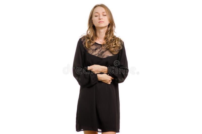 Una ragazza in un vestito nero sta tenendo un dolore di ciao-tecnologia nell'addome fotografie stock