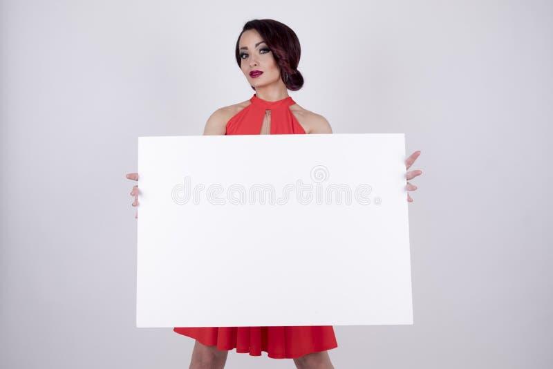 Una ragazza in un vestito rosso con un'insegna immagini stock