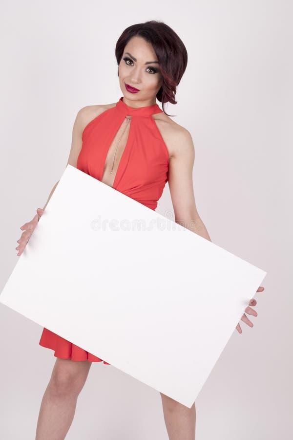 Una ragazza in un vestito rosso con un'insegna immagini stock libere da diritti