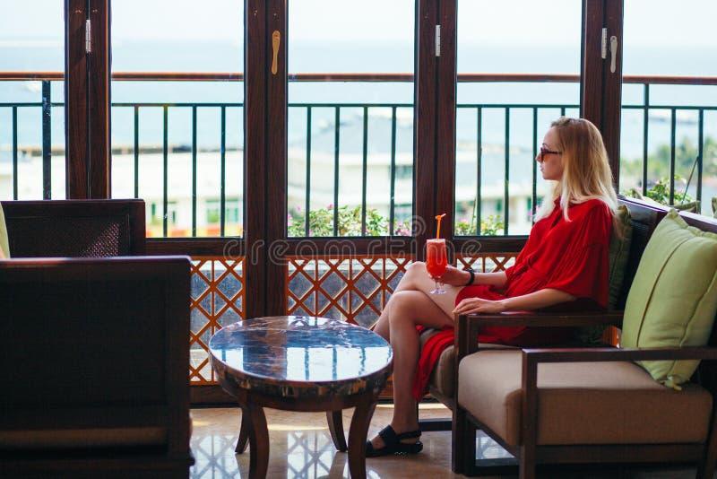 Una ragazza in un vestito rosso sta bevendo un cocktail rosso nell'ingresso dell'hotel Una donna bionda in occhiali da sole è fotografia stock libera da diritti