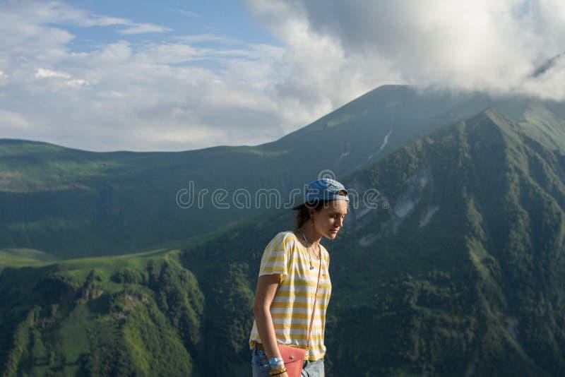 Una ragazza in una maglietta a strisce ed in un cappuccio di estate sulle montagne di fiaba e su un fondo misterioso del cielo fotografia stock