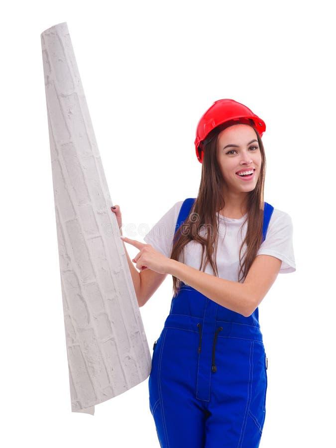 Una ragazza in uniforme ed in un casco, sta indicando ad un rotolo della carta da parati che tiene Isolato su bianco immagini stock