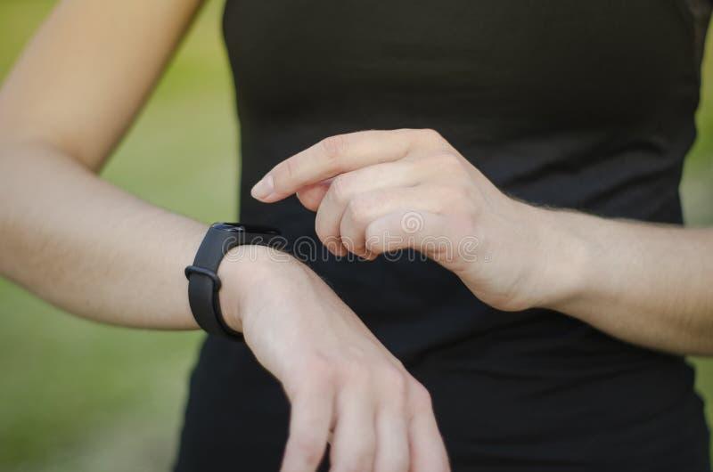 Una ragazza usa un inseguitore di forma fisica SmartWatch fotografia stock