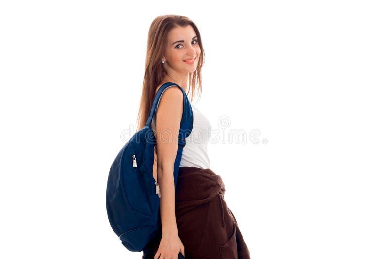 Una ragazza vale la pena di girare lateralmente e tiene la cartella della spalla isolata su fondo bianco fotografia stock