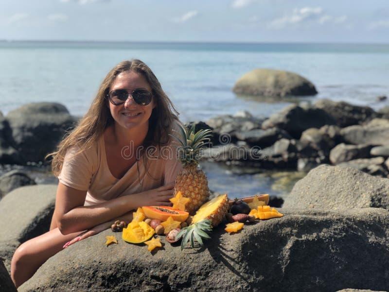 Una ragazza vegetariana dalla carnagione chiara si siede davanti al mare ed il cielo blu nuvoloso ed il sorriso contro lo sfondo  fotografia stock libera da diritti
