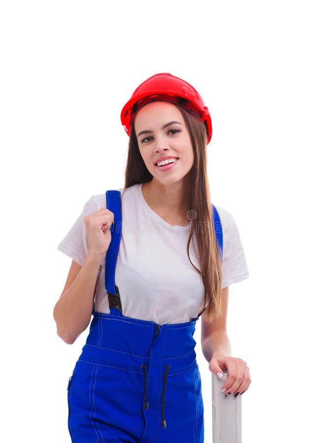 Una ragazza, vestita in un'uniforme ed in un casco, aderisce ad un rotolo della carta da parati e sorride Isolato immagine stock libera da diritti