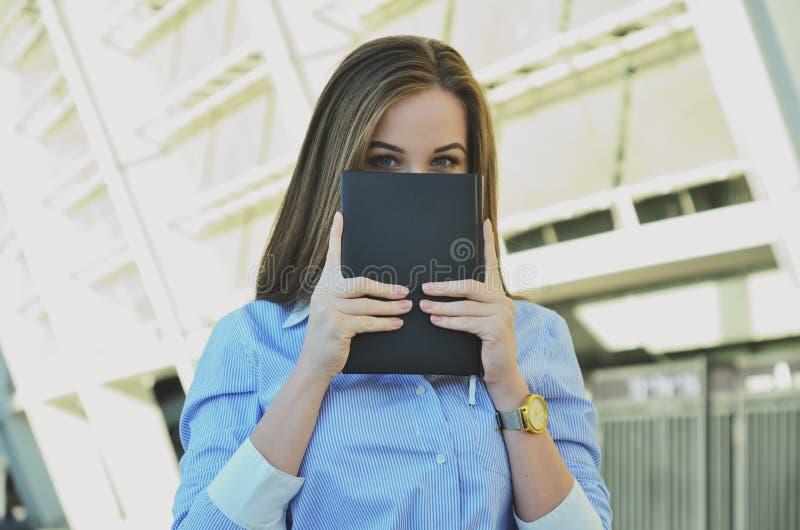 Una ragazza in vestiti dell'ufficio tiene un taccuino con le sue mani fotografie stock