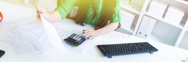 Una ragazza in vetri lavora nell'ufficio con un computer, un calcolatore ed i documenti immagine stock libera da diritti