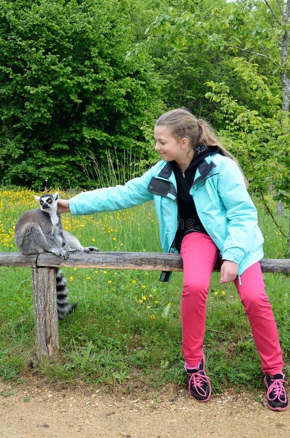 Una ragazza vicino alle lemure addomesticate immagine stock