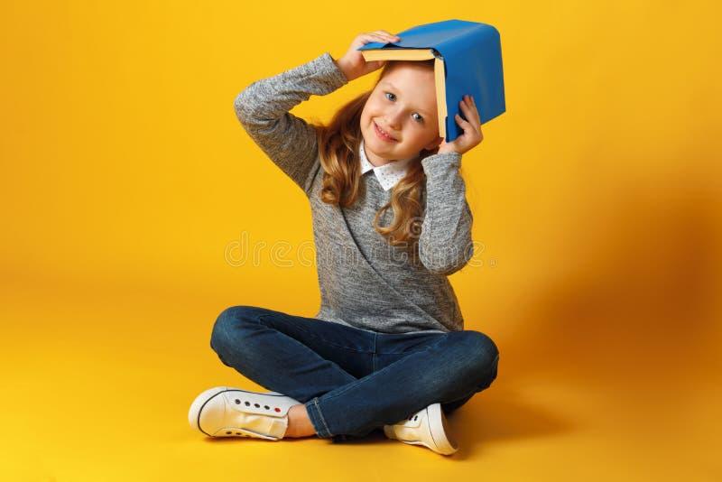 Una ragazzina allegra è seduta sul pavimento con un libro sulla testa Concetto di istruzione e scuola immagini stock