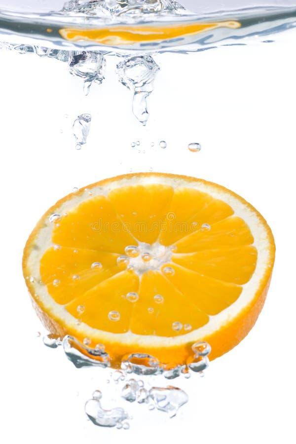 Una rebanada anaranjada que cae en agua foto de archivo libre de regalías