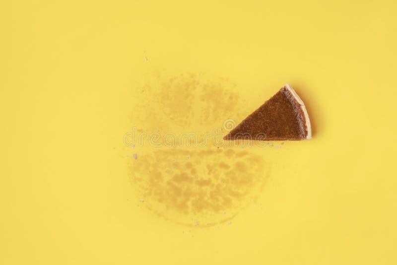 Una rebanada de empanada en fondo amarillo foto de archivo