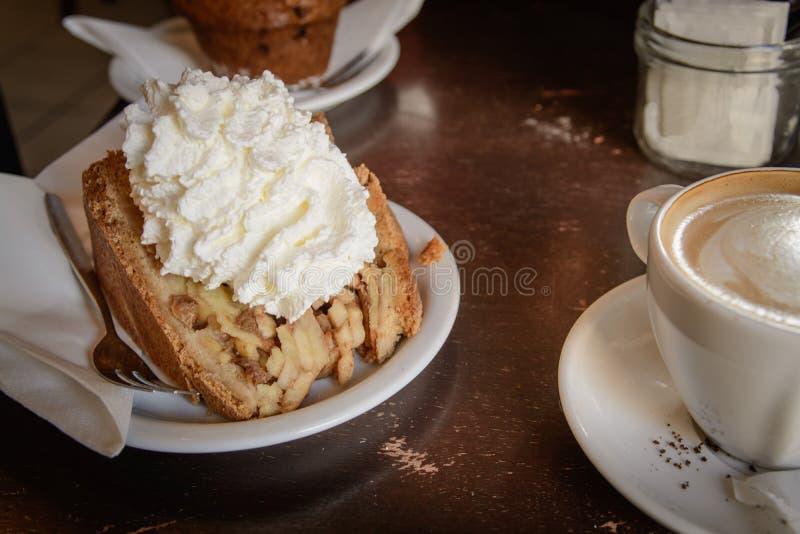 Una rebanada de empanada de manzana con crema azotada y un café del capuchino en una tabla de madera foto de archivo libre de regalías