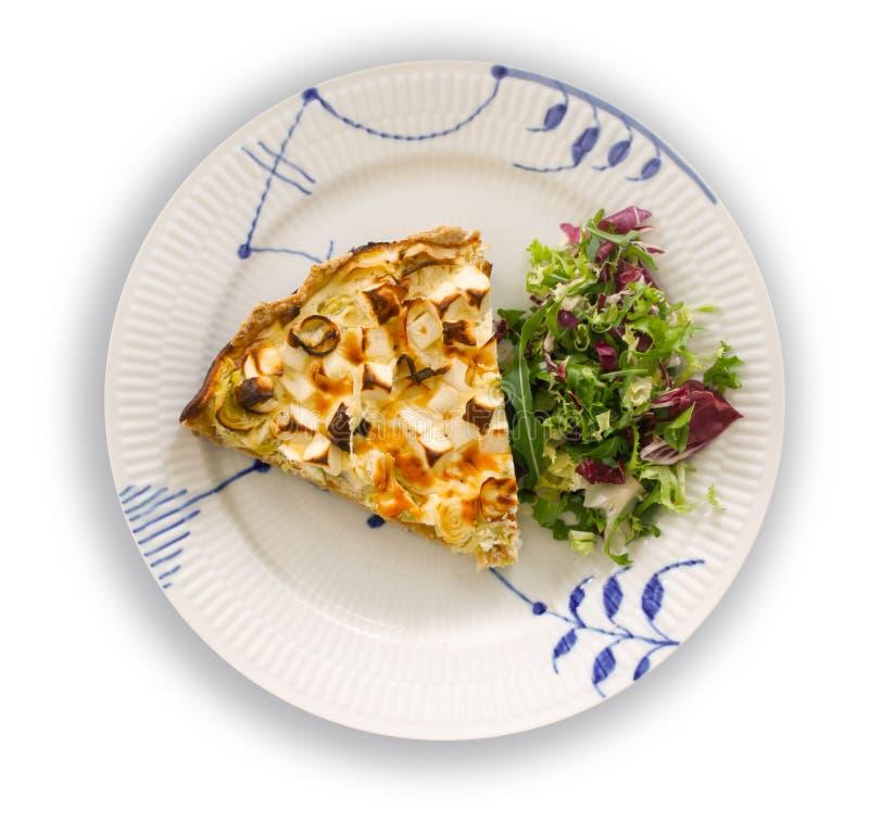 Una rebanada de quiche con el puerro y el queso Feta o el queso de cabras en una placa con la ensalada verde de la hoja curruscan imagen de archivo