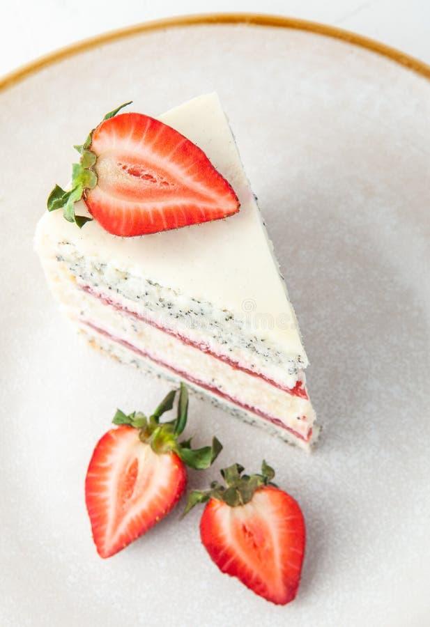 Una rebanada de torta de la fresa en una placa gris Adornado con las fresas Visi?n desde arriba En un fondo blanco fotografía de archivo