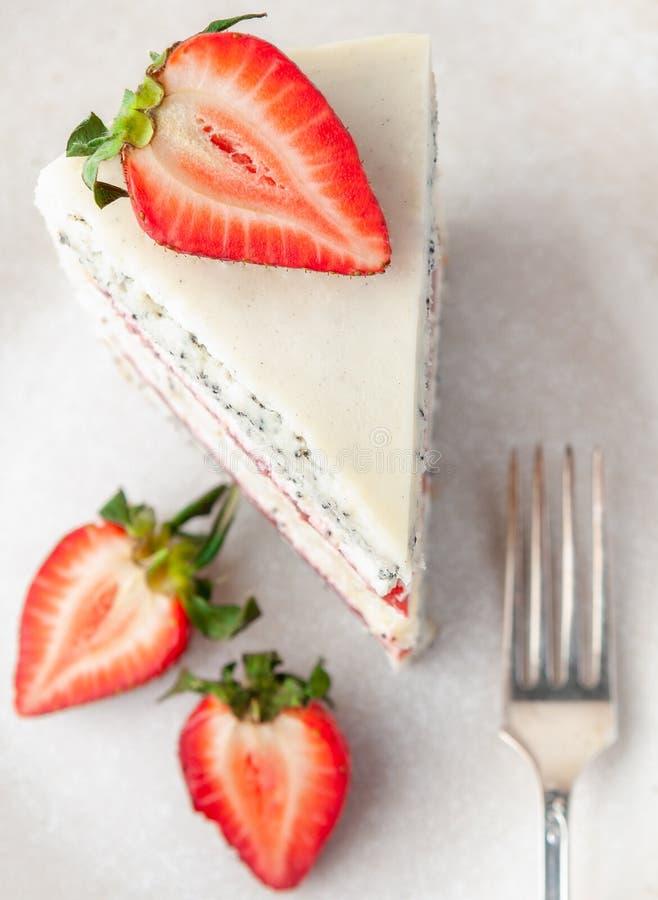 Una rebanada de torta de la fresa en una placa gris Adornado con las fresas Visi?n desde arriba En un fondo blanco fotos de archivo libres de regalías